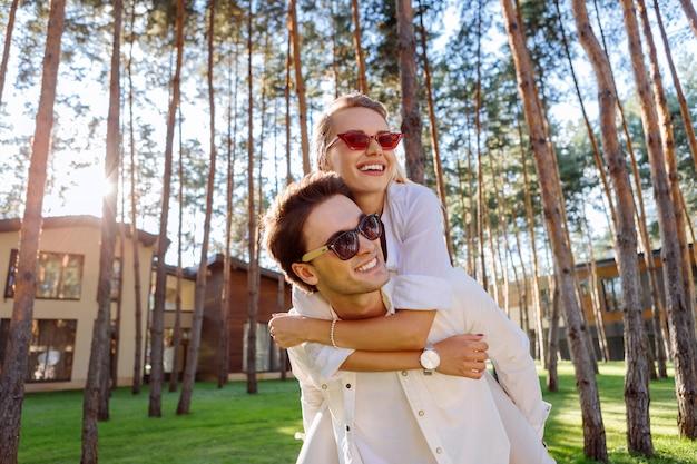Piękny dzień. wesoła pozytywna kobieta przytula męża, czując się razem z nim szczęśliwa