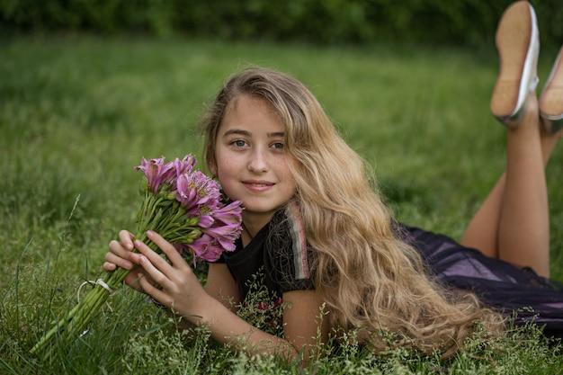 Piękny dziewczyny lying on the beach na trawie, ono uśmiecha się podczas gdy trzymający kwiaty outside w czarnej koszulce podczas dnia.