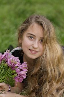 Piękny dziewczyny lying on the beach, ono uśmiecha się podczas gdy trzymający kwiaty outside w czarnej koszulce podczas dnia.