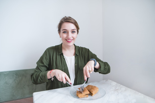 Piękny dziewczyny obsiadanie w restauraci i łasowanie kanapka z nożem i rozwidleniem. obiad w lekkiej kawiarni.