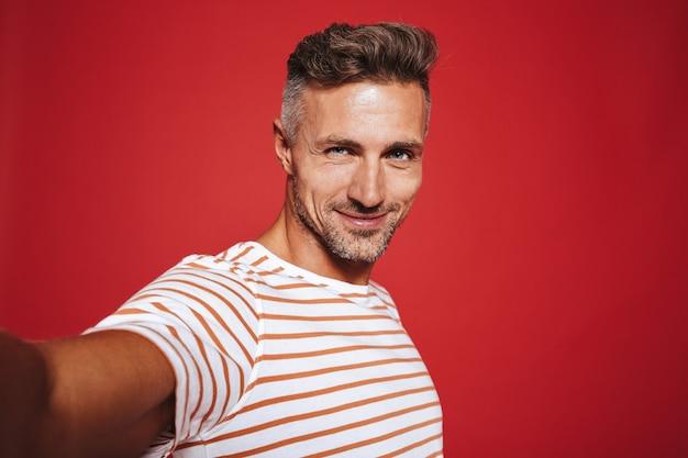 Piękny facet 30s w pasiastym t-shircie uśmiechający się podczas robienia zdjęcia selfie na czerwonym tle