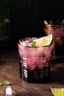 Piękny fioletowy kieliszek koktajlu z whisky, lodem i limonką