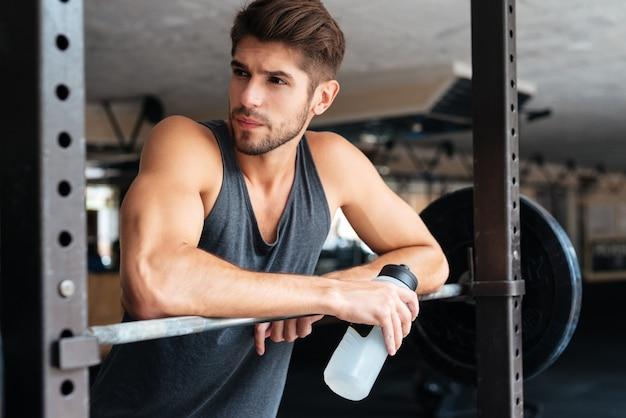 Piękny fitness człowiek z ciężarami odwracając. z butelką