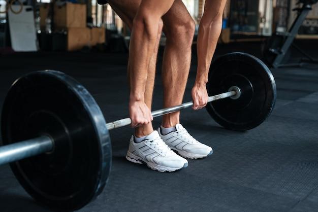 Piękny fitness człowiek z ciężarami, robienie ćwiczeń. ściąganie sztangi z podłogi