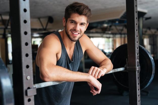 Piękny fitness mężczyzna z ciężarami. uśmiechnięty.