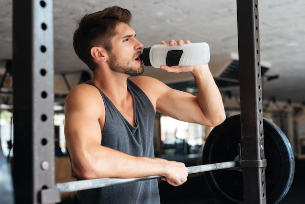 Piękny fitness mężczyzna z ciężarkami wody pitnej. po treningu