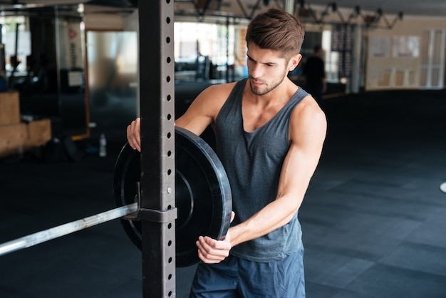 Piękny fitness mężczyzna ze sztangą. rozważny