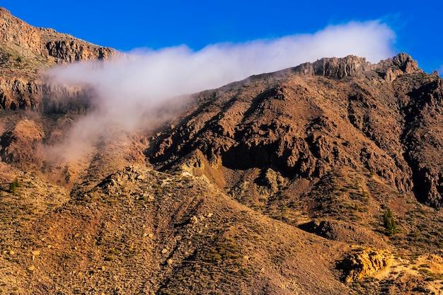 Piękny górski krajobraz backgorund ze skalistym szczytem i błękitnym niebem z białymi chmurami