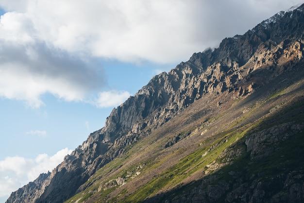 Piękny górski krajobraz z wysokim zielonym zboczu góry z ostrymi skałami w słońcu. klimatyczna sceneria górska ze stromym zboczem w słońcu. niesamowity słoneczny widok na wielką górę i niskie chmury.