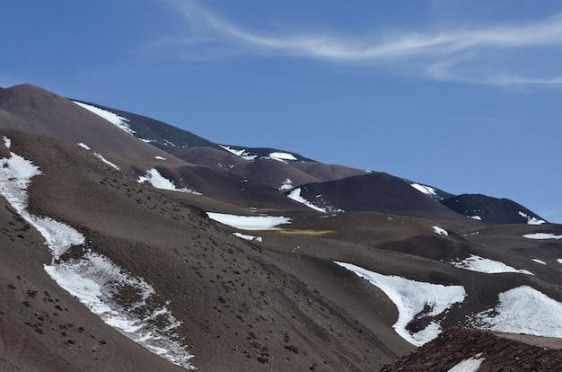 Piękny górzysty krajobraz częściowo pokryty śniegiem pod jasnym niebem
