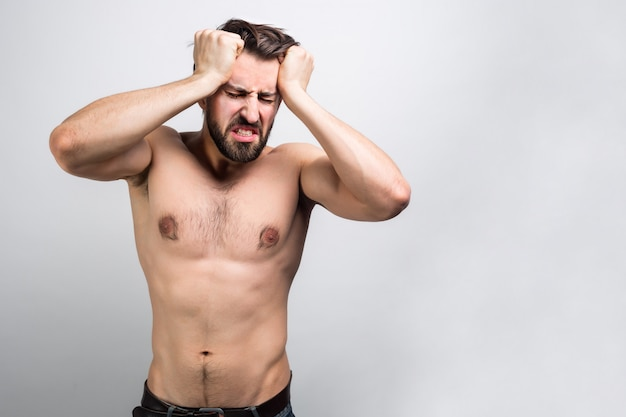 Piękny i atrakcyjny prawie nagi mężczyzna stoi przy ścianie i cierpi na bóle głowy. prawdopodobnie zaraz zachoruje.