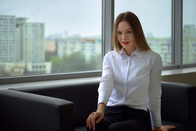 Piękny i pozytywny bizneswoman na kanapie patrzeje prosty i uśmiechnięty, okno z pejzażem miejskim na ścianie