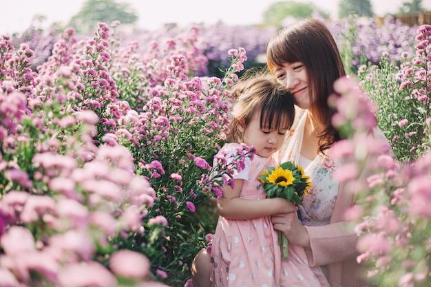 Piękny i romantyczny obraz matki i jej małych dzieci bawiących się razem w ogrodzie kwiatowym.