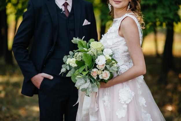 Piękny i wyrafinowany bukiet ślubny trzyma pannę młodą w dłoniach obok pana młodego. bukiet ślubny i pierścienie.