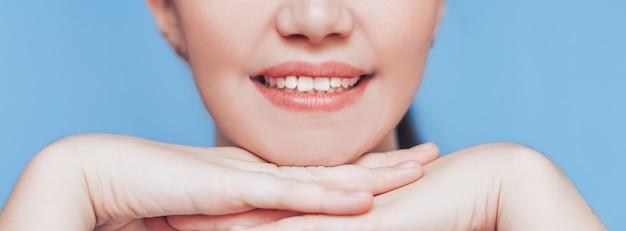 Piękny idealny uśmiech młodej kobiety.