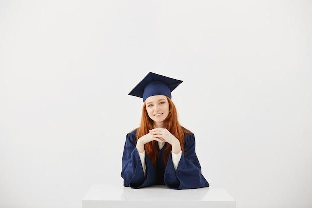 Piękny imbir absolwent uśmiecha się.