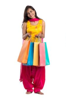 Piękny indiański młodej kobiety mienie i pozować z torba na zakupy na bielu
