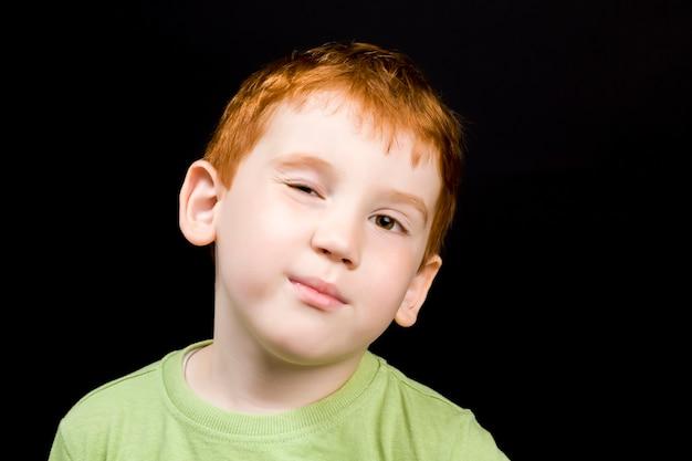 Piękny, inteligentny chłopiec mruga okiem, zbliżenie portret uroczego rudowłosego dziecka