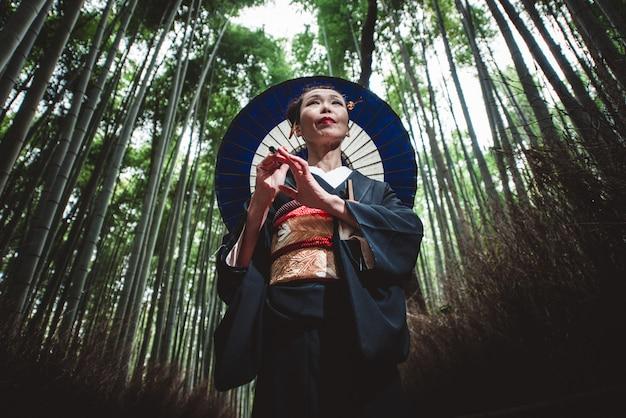 Piękny japoński starszy kobiety odprowadzenie w bambusowym lesie