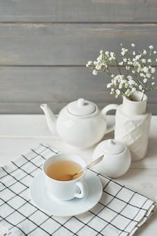 Piękny jasny zestaw herbaty. białe ceramiczne dzbanki i składniki herbaty, na białym stole.