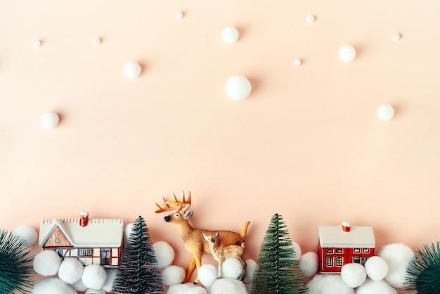 Piękny jeleń w wigilię bożego narodzenia na tle wiejskich domów, makieta świąteczna