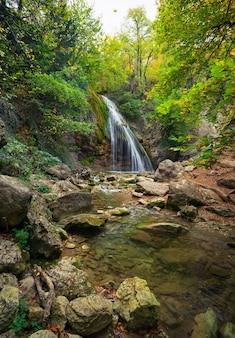Piękny jesienny krajobraz z wodospadem, drzewami i kamieniami