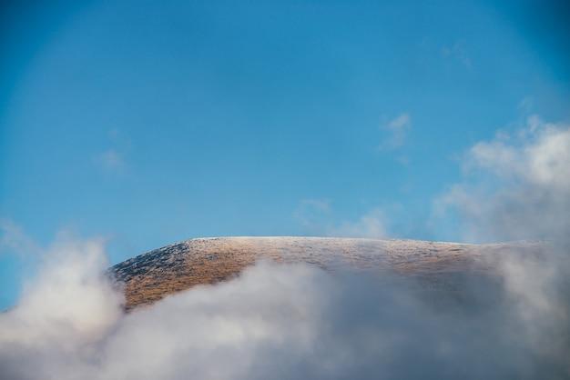 Piękny jesienny krajobraz ze złotym szczytem góry z białym śniegiem wśród gęstych chmur na niebieskim niebie. malowniczy widok z góry w gęstych niskich chmurach. kolorowe alpejskie krajobrazy z niskimi chmurami w górach.