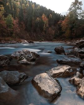 Piękny jesienny widok na przepływającą rzekę między skałami