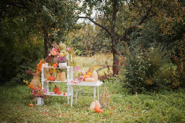 Piękny jesienny wystrój z kwiatami, jagodami, dyniami w ogrodzie