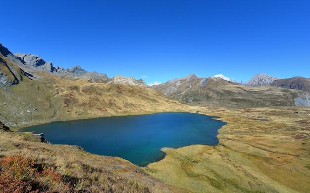 Piękny jezioro w wysokogórskiej górze w jesieni pod niebieskim niebem