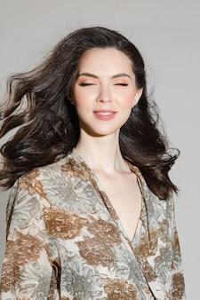 Piękny kaukaski kobieta z kręconymi włosami uśmiecha się na białym tle
