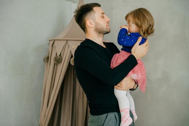 Piękny kaukaski mężczyzna gra z małą córeczką.