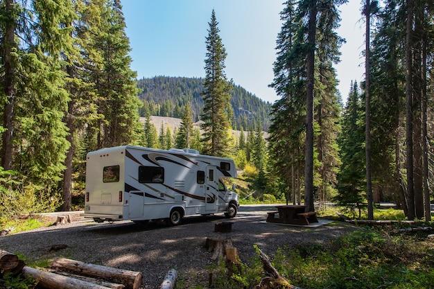 Piękny kemping w górach z kamperem i drewnianą ławką.