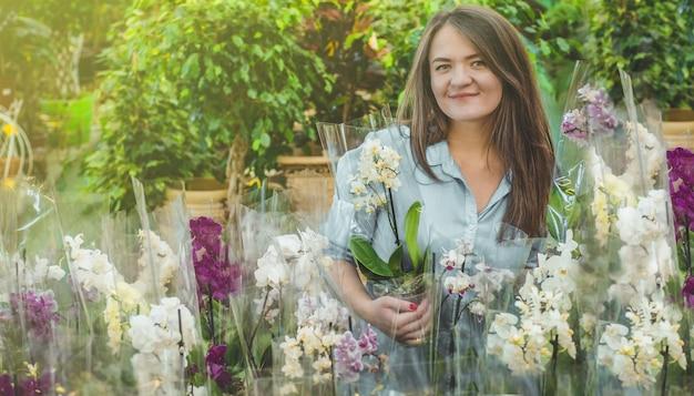 Piękny klient płci żeńskiej zapachu kolorowych kwitnących orchidei w sklepie. ogrodnictwo w szklarni. ogród botaniczny, hodowla kwiatów, koncepcja przemysłu ogrodniczego