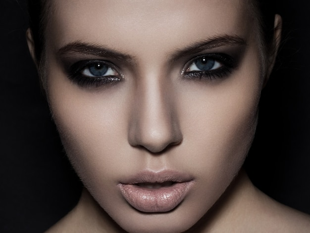 Piękny kobieta modela smokey oczu makeup zakończenie up na czarnym tle