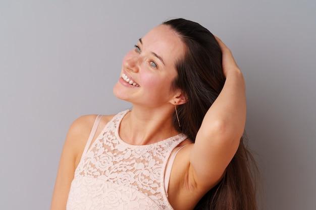 Piękny kobieta nastolatek pozuje nad szarym tłem