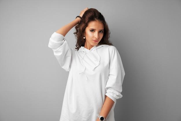 Piękny kobieta nastolatek w białym hoodie pozuje nad szarym tłem