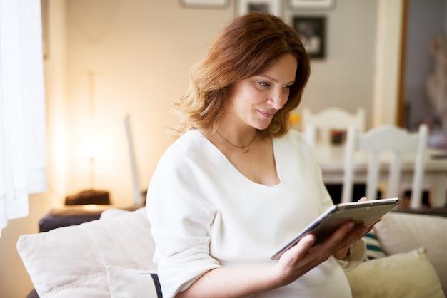 Piękny kobieta w ciąży patrzeje pastylkę podczas gdy siedzący na kanapie w domu.
