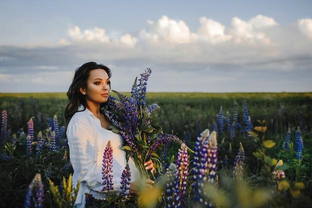 Piękny kobieta w ciąży stoi wśród pola łubinów na niebie