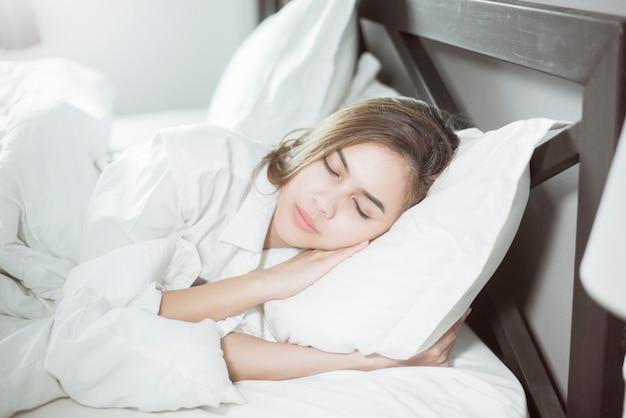 Piękny kobiety dosypianie na łóżku