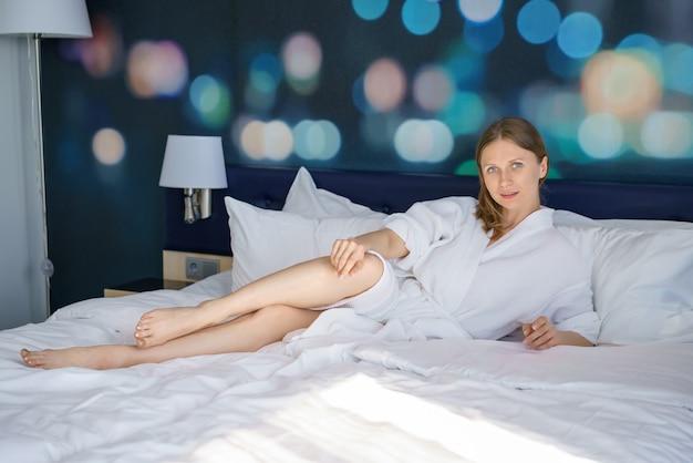 Piękny kobiety lying on the beach na łóżku w łóżku w domu