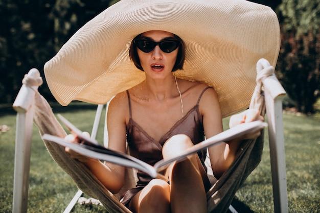 Piękny kobiety lying on the beach w hamaku jest ubranym dużego sunhat