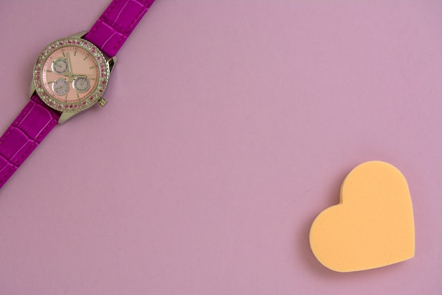 Piękny kobiety nadgarstku zegarek i serce kształtująca makeup gąbka na purpurowym papierowym tle.