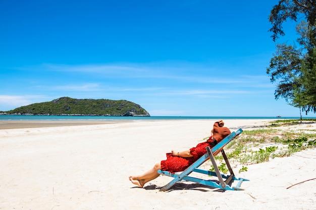 Piękny kobiety obsiadanie w krześle przy morzem w lecie