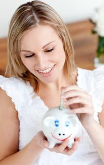 Piękny kobiety oszczędzania pieniądze w prosiątku