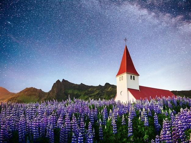 Piękny kolaż kościół luterański w vik pod fantastycznym gwiaździstym niebem. islandia