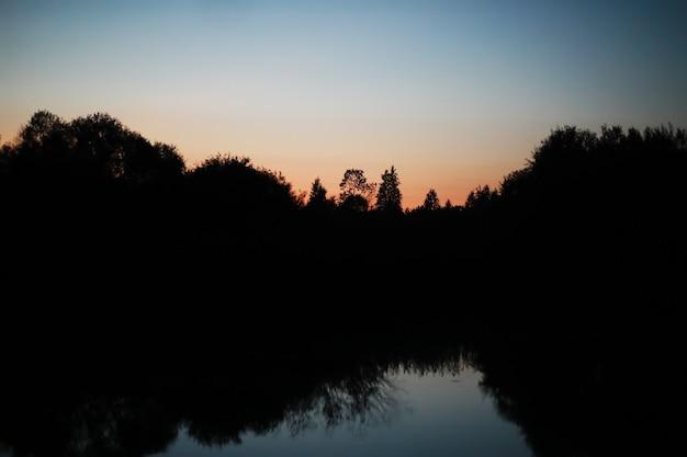 Piękny kolor nocnego nieba rzeki. jasny księżyc. chmury i gwiazdy w wysokich górach.