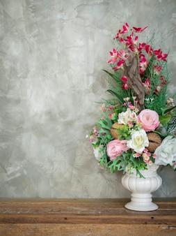 Piękny kolorowy bukiet kwiatów w biały wazon vintage ozdoba na drewnianym stole na tle ściany betonowej loft stylu z miejsca kopiowania, styl pionowy.