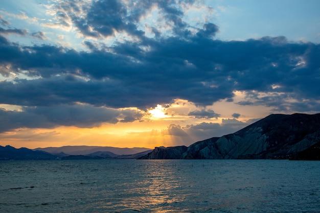 Piękny kolorowy wschód słońca nad morzem z dramatycznymi chmurami i świecącym słońcem