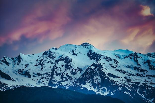 Piękny kolorowy zachód słońca nad ośnieżonym pasmem górskim. krajobraz przyrody. dramatyczne zachmurzone różowe niebo. wakacje, podróże, sport, rekreacja. park narodowy kazbegi, gergeti, gruzja. retro filtr tonujący